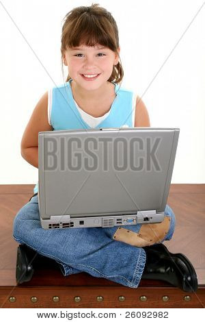 Beautiful Little Girl Working On Laptop Computer. Sitting crossed leg on a table.  Shot in studio over white.