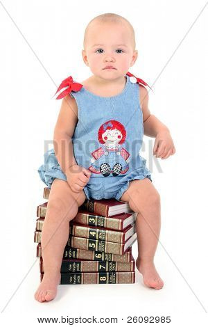 Beautiful 10 Month Old Baby Girl On Stack Of Encyclopedias. Shot in studio over white.