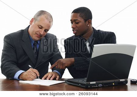 Two men in suits at desk signing papers.  Shot in studio over white.