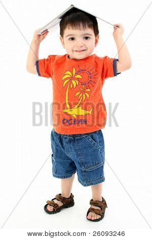 Adorable toddler boy in casual wear standing with book on his head.  Full body shot in studio over white.