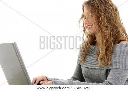 Beautiful 16 Year Old Teen Working On Laptop. Wearing grey sweater with long curly blonde hair.  Shot in studio over white.