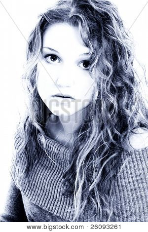 Dramatic Portrait of Sixteen Year Old Girl in Blue tones. Shot in studio over white.