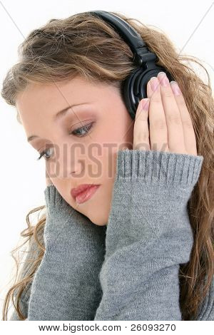 Beautiful sixteen year old teen girl listening to headphones. Shot in studio over white.