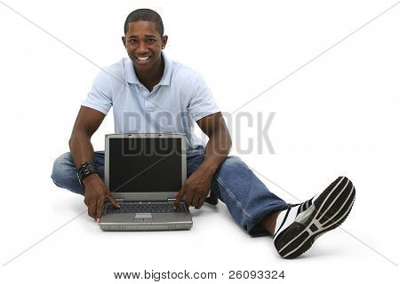 Attractive young man sitting on floor with laptop computer. Shot in studio over white.