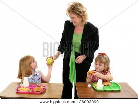 Pretty little girl handing the teacher an apple at lunch time. Back to School.