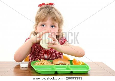 Small girl with blonde hair and big blue eyes having lunch at school.