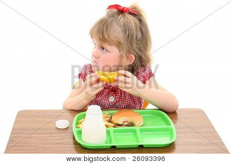 Little girl not happy with her school lunch.  Adorable sad look on face while holding orange slice.