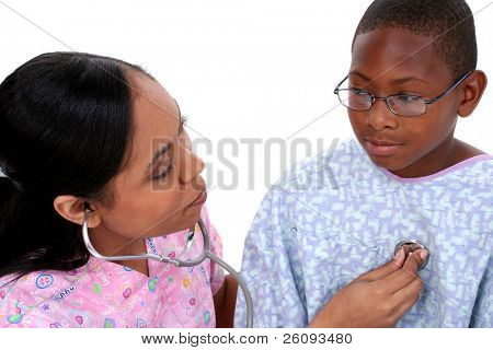 Beautiful nurse in pink scrubs listening to boy's heart with stethoscope.  Boy wearing standard American hospital gown and glasses.