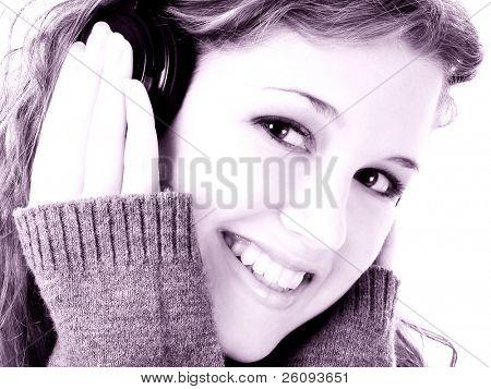 Dezesseis ano de idade linda menina adolescente escutando fones de ouvido. Filmado em estúdio sobre branco.