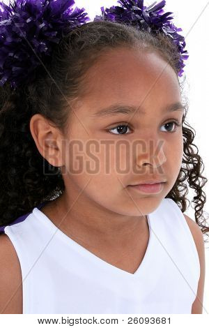Close Up Six Year Old Girl In Cheerleading Uniform with mini pompoms in hair. Shot in studio over white.
