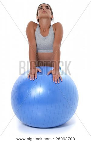 Beautiful teen girl in workout clothes stretching on exercise ball.  Shot in studio over white.