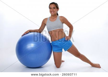 Teen girl leaning on exercise ball.  Wearing workout clothes and barefoot.