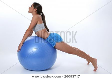 Teen girl in workout clothes stretching over exercise ball.