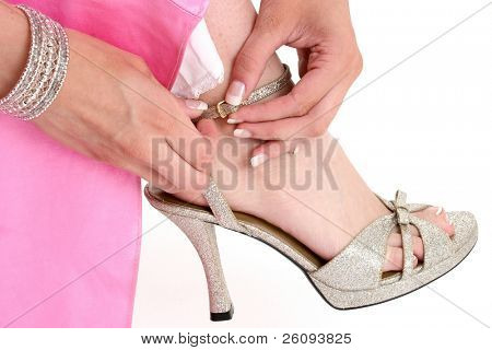 Manicured woman's hands buckling golden formal dress shoe