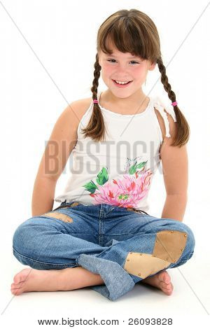 Little girl in braids sitting barefoot on white floor. Shot in studio.
