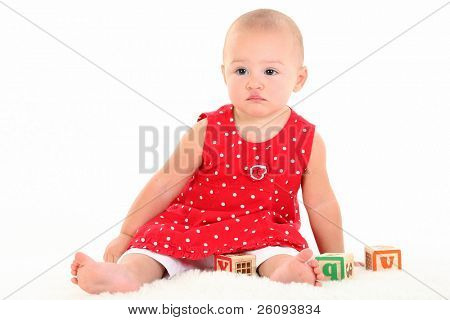 Beautiful Baby Girl with Stork Bite on Upper Lip.  Sitting on white blanket playing with blocks.  Serious expression.