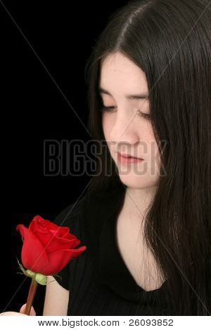 Beautiful young girl with long black hair and pale complexion looking at red rose.  Shot in studio over black.