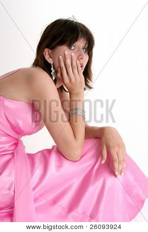 Beautiful sixteen year old girl in pink formal or prom dress. Dark hair and blue eyes. Shot in studio over white.