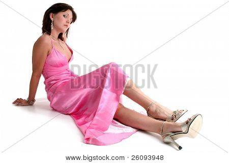 Beautiful sixteen year old teen in pink formal and glitter high heels.  Shot in studio over white.