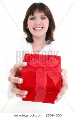 Beautiful young woman holding red gift box.  Over white. Focus on Box and Hands.  FAce out of focus.