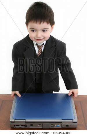 Toddler boy in suit at laptop computer at desk. Shot over white.