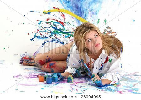 """Beautiful young woman laying in paint covered studio.  Paint splattered on walls, floor, model.  Shot in studio over """"white"""".  :)"""