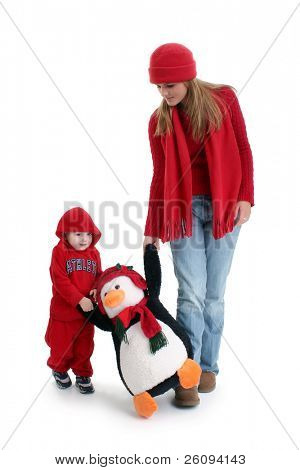 Young woman and toddler boy out shopping for toys.  Walking with a giant stuffed pinquin. Shot in studio.