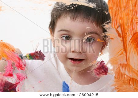 Adorable Toddler Boy Painting On Glass. Shot through glass over white background.