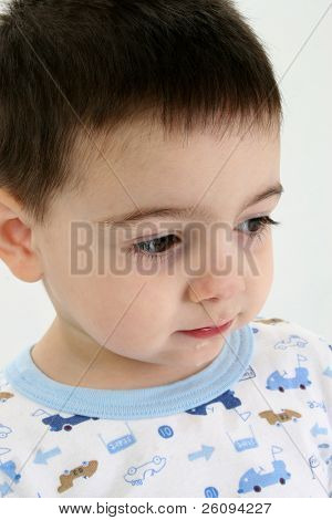 Toddler boy in pajamas with runny nose and drool on face.  Sad expression, circles under eyes. Shot in studio.