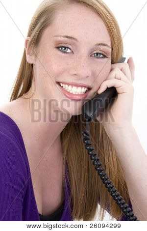 Beautiful fourteen year old girl laughing on telephone. Shot in studio over white.