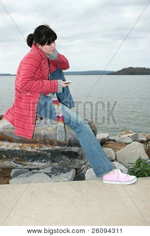 Beautiful young woman sitting on rock by the lake listening to digital music on headphones.