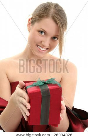 Young teen girl in red formal dress handing camera a holiday present.  Shot in studio over white.