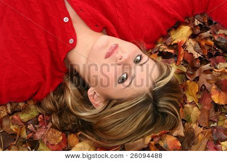 Beautiful young woman in red sweater laying in a bed of fall colored leaves.