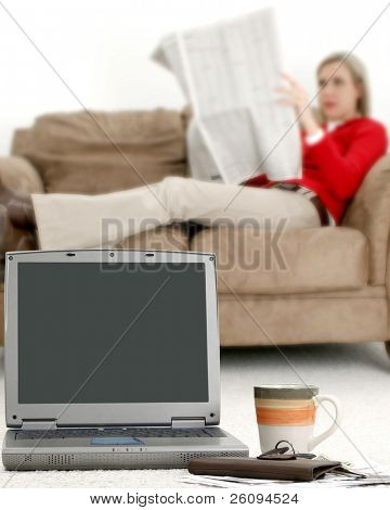 Casual young woman taking a break from computer and bills.  Focus on computer.