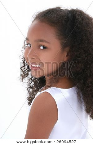 Profile of beautiful little six year old girl looking over shoulder.  Wearing white dress over white.