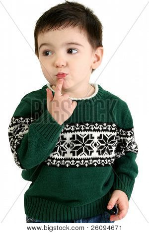 Small boy trying to decide what he wants for Christmas this year.  Wearing green holiday sweater and jeans.