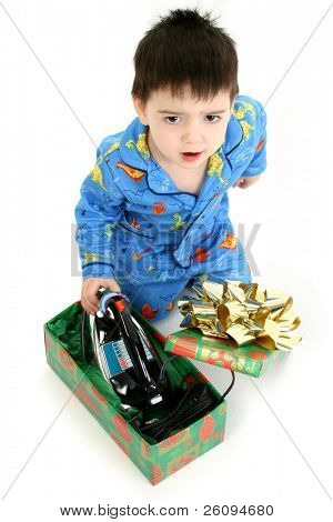 Adorable shot of a very angry two year old boy in pajamas opening and hating his new iron. ???