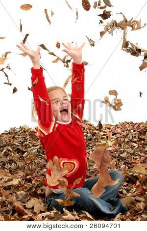 Happy 7 year old girl playing in a big pile of dried leaves. Shot in studio over white.