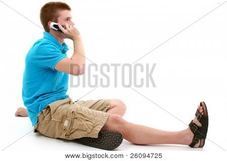 Casual teen boy sitting on  talking on cellphone.