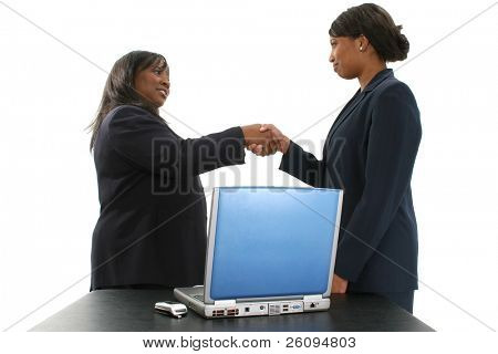 Two beautiful African American business women shaking hands.  Standing behind a table with laptop and cellphone.  Over white background.  Women in mid and late 20's.