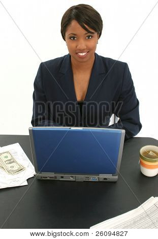 Beautiful African American Woman in suit at table with laptop, newspaper, money, bills, cup of green tea.