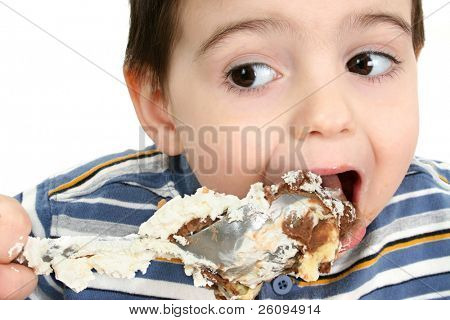 Close up of a two year old boy eating possum pie with a big silver spoon. Shot in studio over white.