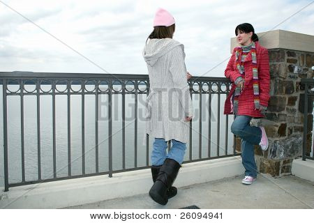 Two beautiful young women in winter clothes outside at the lake talking on a cold hazy day.