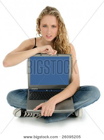 Beautiful Young girl with angry expression holding laptop screen towards camera.  Shot over white in studio.