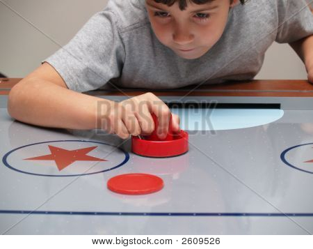A Young Boy Playing Air Hockey