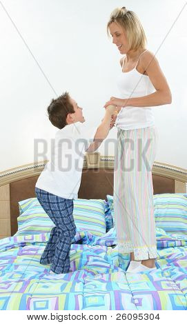 Mom and son in pajamas playing in bed.