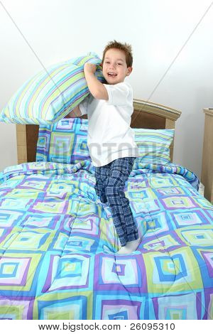 Happy five year old boy throwing pillow towards camera.