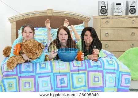 Three teen girls with snacks, drinks and remote control in bed watching tv.