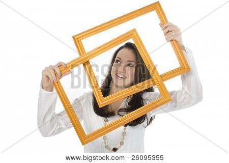 Beautiful young woman holding two wooden frames in front of her face. Shot in studio over white.