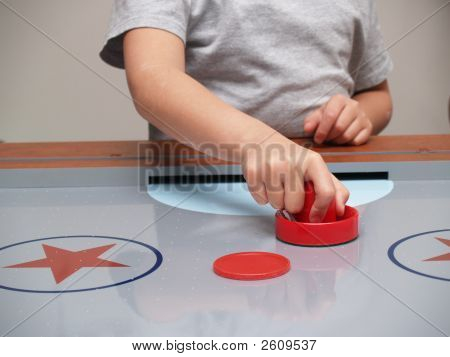 A Hand On A Red Mallet On An Air Hockey Table